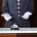 Portvakt som pekar till hotellklockan Arkivfoto