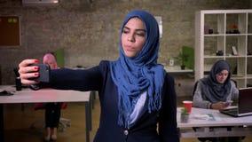 Poruszająca śliczna arabska kobieta w hijab obrazkach na ona telefon podczas gdy stojący w ceglanym biurze przed jej działaniem