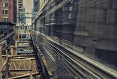 Poruszający pociąg na podwyższonych śladach wśród budynków przy pętli, szkła i stali mostem między budynkami, Lon - Chicagowski c Zdjęcia Stock