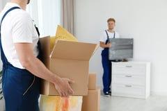 Poruszający usługowy pracownik z pudełkiem i jego kolegą w pokoju fotografia stock
