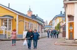 Porvoo. Finland. People in the Old Town. PORVOO, FINLAND - OCTOBER 18, 2015: Street in Old Town with small shops and cafes. On the background is the Old Town royalty free stock photo