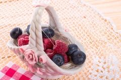 Porzelan basket with raspberry and bilberry Stock Photo