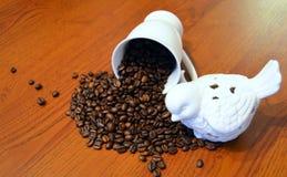 Porzellanfigürchenvögel mit Kaffeebohnen werden auf den Holztisch zerstreut Stockbilder