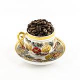 PorzellanKaffeetasse füllte mit den Kaffeebohnen, die auf Weiß lokalisiert wurden Stockfoto