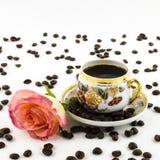 PorzellanKaffeetasse mit rosafarbener Blume und Kaffeebohnen Stockbilder