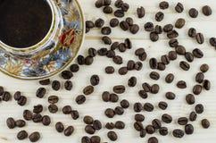 PorzellanKaffeetasse und Kaffeebohnen auf Holztisch Lizenzfreies Stockbild