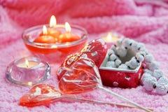 Porzellankasten, -lolipops und -kerzen in Form von Herzen auf einem rosa Hintergrund Romantisches Konzept des Valentinsgruß-Tages Stockbild
