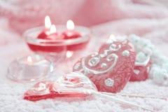 Porzellankasten, -lolipops und -kerzen in Form von Herzen auf einem rosa Hintergrund Romantisches Konzept des Valentinsgruß-Tages Lizenzfreie Stockfotos