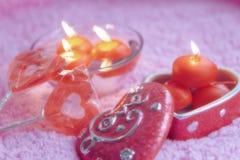 Porzellankasten, -lolipops und -kerzen in Form von Herzen auf einem rosa Hintergrund Romantisches Konzept des Valentinsgruß-Tages Lizenzfreies Stockfoto