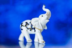Porzellanstatuette, Porzellanstatuette des Elefanten auf einem blauen Hintergrund Stockbilder