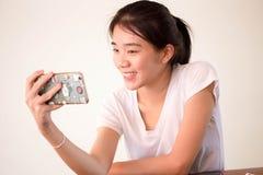 Porzellanstudentenhochschulschönes Mädchen Asiens thailändische, das ihr intelligentes Telefon Selfie verwendet Stockfotografie