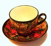 Porzellantasse und untertasse von einem Teesatz umfasst in der russischen Art in Khokhloma stockfotografie