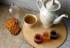 Porzellanteekessel und -Teetasse mit grünem Tee auf einem hölzernen Hintergrund Stockfotos