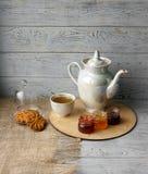 Porzellanteekessel und -Teetasse mit grünem Tee Gepresste Rosen auf einem Holztisch Drei kleine Gläser der selbst gemachten Beere Stockfoto