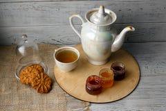 Porzellanteekessel und -Teetasse mit grünem Tee Gepresste Rosen auf einem Holztisch Drei kleine Gläser der selbst gemachten Beere Stockbilder