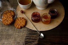 Porzellanteekessel und -Teetasse mit grünem Tee Gepresste Rosen auf einem Holztisch Drei kleine Gläser der selbst gemachten Beere Stockbild
