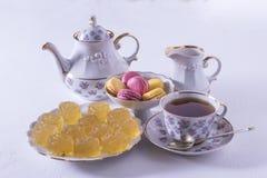 Porzellanteesatz mit Milch, Makkaroni und Marmelade, Milchkrug, Teeschale, Tasse und Untertasse, gummiartige Süßigkeit stockfotografie