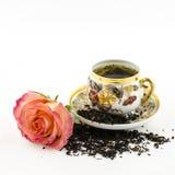 Porzellanteeschale mit rosafarbener Blume und trockenen Teeblättern Stockfotografie