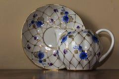 Porzellanzuckerschüssel, Schale, Milch, Teller mit goldenem Muster und blaue Blumen Stockfoto