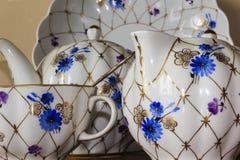 Porzellanzuckerschüssel, Schale, Milch, Teller mit goldenem Muster und blaue Blumen Lizenzfreies Stockbild