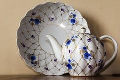 Porzellanzuckerschüssel, Schale, Milch, Teller mit goldenem Muster und blaue Blumen Stockfotografie