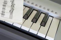 Porzion av det elektroniska tangentbordet och den musikaliska ställningen Arkivbilder