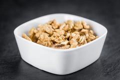 Porzione di noci incrinate su una lastra dell'ardesia Fotografia Stock