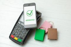 POS终端,有手机的付款机器在白色背景 与NFC技术的不接触的付款 被批准的付款 免版税库存图片