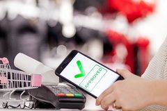 POS τερματικό, μηχανή πληρωμής με το κινητό τηλέφωνο στο υπόβαθρο καταστημάτων Ανέπαφη πληρωμή με την τεχνολογία NFC ελεύθερη απεικόνιση δικαιώματος
