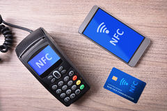POS card and mobile on wood table nfc transmision system. Mobile phone and credit card on wood table. Nfc concept of payment system. Top view Royalty Free Stock Images