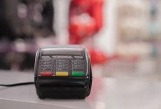 POS payment terminal on white table in shop royalty free stock photos