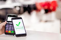 POS terminal, Payment Machine with mobile phone on store background. Contactless payment with NFC technology.  royalty free stock photography