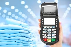 POS terminal in woman`s hands against shop background with pile of clothes, demonstrates cashless payment. Credit card machine. Ca. Rd payment terminal Stock Image
