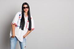Posa alla moda della giovane donna della parete grigia Fotografie Stock