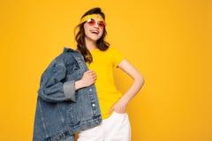 Posa allegra della ragazza dei pantaloni a vita bassa isolata su giallo fotografia stock