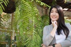 Posa asiatica della donna al caffè all'aperto giovane adulto femminile con il natura Immagini Stock Libere da Diritti