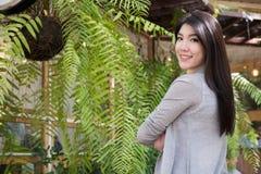 Posa asiatica della donna al caffè all'aperto giovane adulto femminile con il natura Fotografie Stock