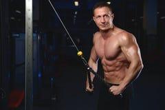 Posa atletica bella e treni dell'uomo di forma fisica nella palestra Immagine Stock Libera da Diritti