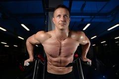 Posa atletica bella e treni dell'uomo di forma fisica nella palestra Immagini Stock Libere da Diritti