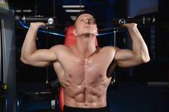Posa atletica bella e treni dell'uomo di forma fisica nella palestra Immagini Stock