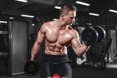 Posa atletica bella e treni dell'uomo di forma fisica nella palestra Fotografie Stock
