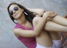 Posa castana attraente con gli occhiali da sole Fotografia Stock Libera da Diritti