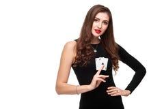 Posa castana sexy con due carte degli assi in sue mani, isolamento dei capelli ricci di concetto della mazza su fondo bianco Immagini Stock
