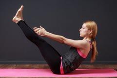 Posa completa della barca Giovane donna bionda che fa esercizio di yoga Immagine Stock