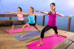Posa del gruppo di yoga della natura variopinto moderno luminoso pacifico di giorno soleggiato all'aperto in nuovo Immagine Stock