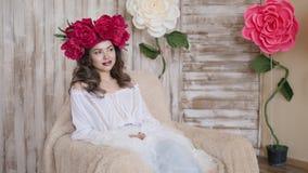 Posa del modello della ragazza una giovane donna in una corona del color scarlatto delle peonie su lei capa, capelli ricci lunghi Immagini Stock