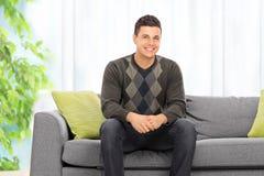 Posa dell'uomo messa su un sofà a casa Immagine Stock