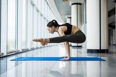 Posa della lucciola La giovane donna esile nella classe di yoga che fa il bello asana si esercita Stile di vita sano nel club di  Immagine Stock