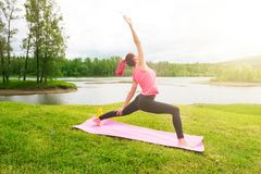 Posa della ragazza di yoga che pratica all'aperto Yoga al parco Concetto dello stile di vita sano Fotografie Stock