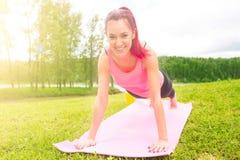 Posa della ragazza di yoga che pratica all'aperto bella ragazza che fa allenamento su erba di mattina Fotografia Stock Libera da Diritti